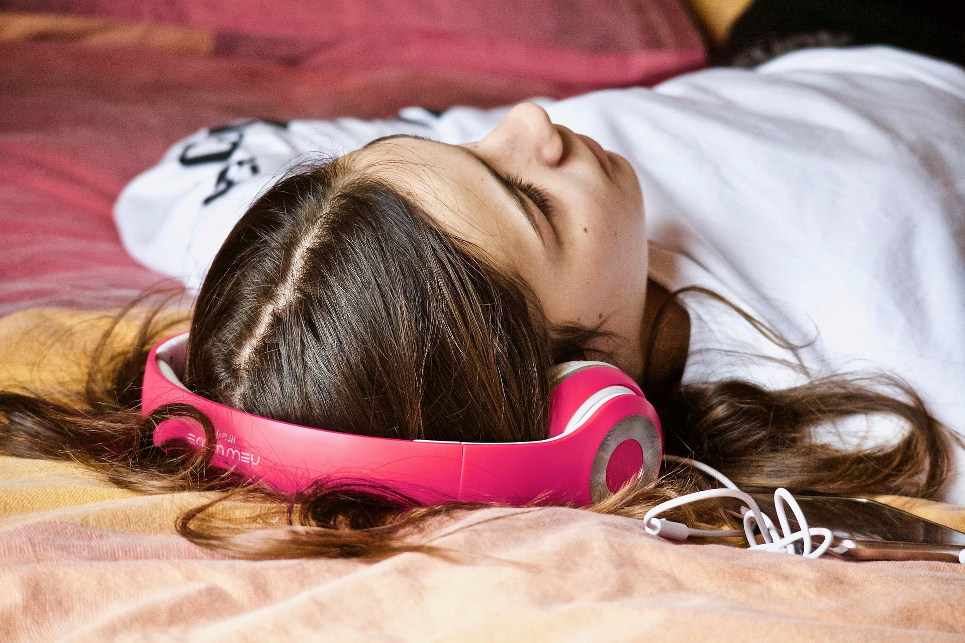 Woman lying on bed wearing pink headphones.