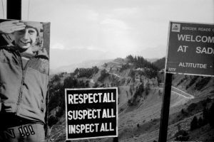 """View of mountains with welcome sign, photo of young boy and sign reading """"respect for all, suspect for all, inspect for all""""."""