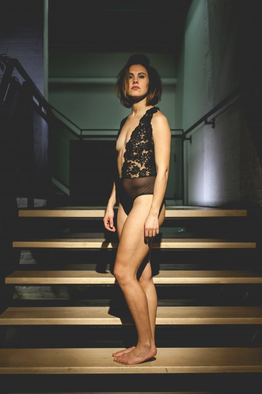 Woman in lingerie standing in staircase.