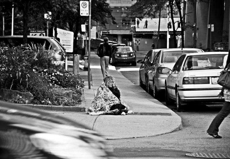 Woman sitting in blanket in middle of sidewalk.