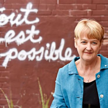"""A blonde, middle-aged white woman standing in front of a brick wall that has the phrase, """"tout est possible"""" in graffiti on it."""