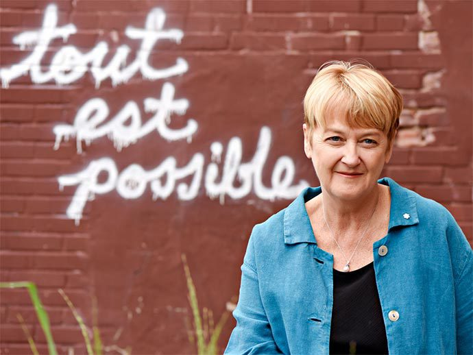"A blonde, middle-aged white woman standing in front of a brick wall that has the phrase, ""tout est possible"" in graffiti on it."