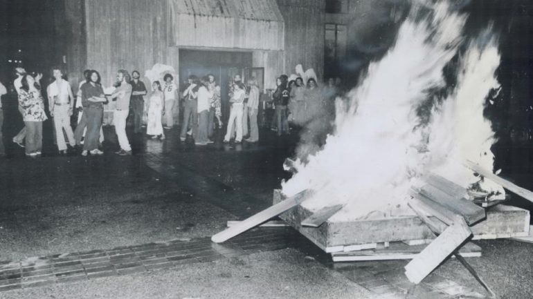 Group of people standing near large pile of burning wood.