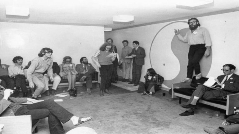 Group standing in large room with Yin-Yang sign on wall and man standing on couch.