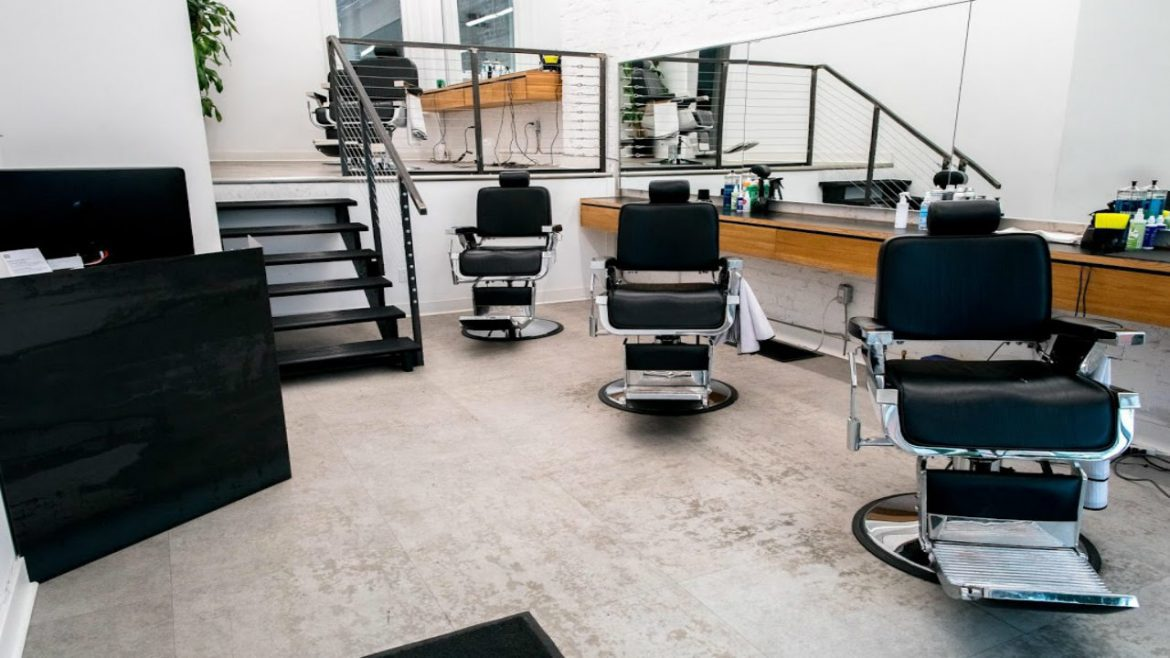 Inside of empty barbershop with four black chairs.