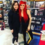 """Two women smiling in front of case reading """"Games Workshop""""."""