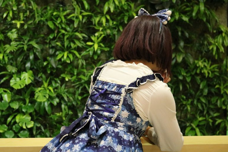 Back of woman with bow in hair.