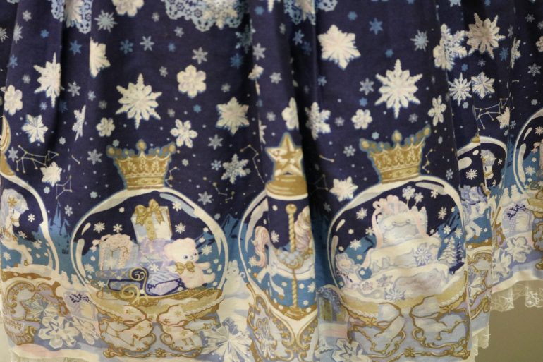 Details of snow globes and snowflakes on bottom of dress.