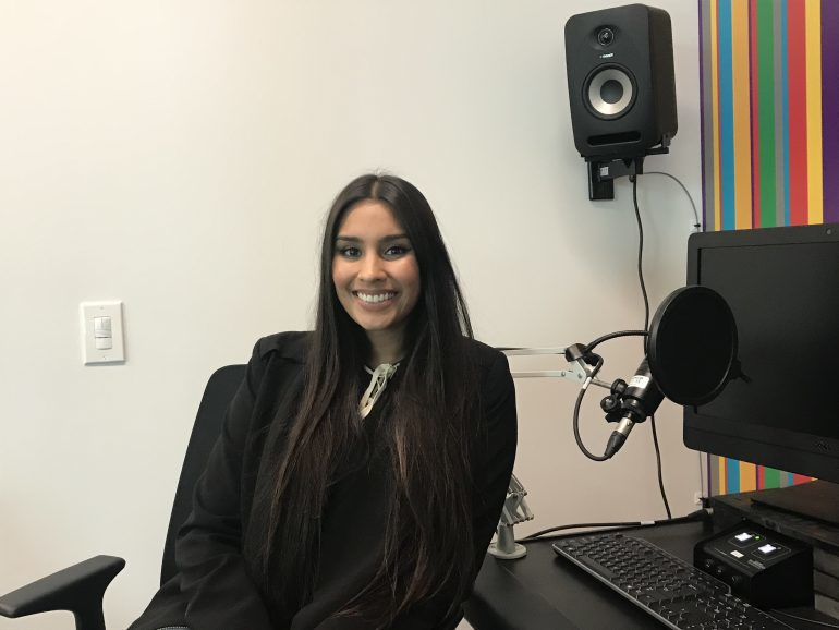 Woman smiling and sitting in recording studio