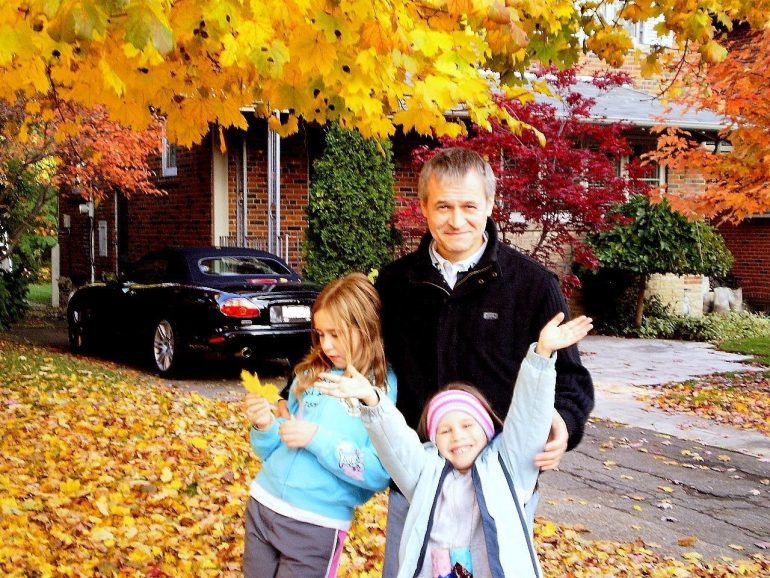 Photo of father and two daughters in leaves outside brick house.