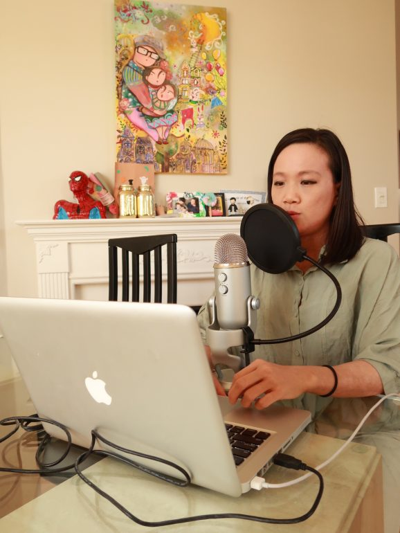 Woman sitting at table in living room with computer speaking into microphone.