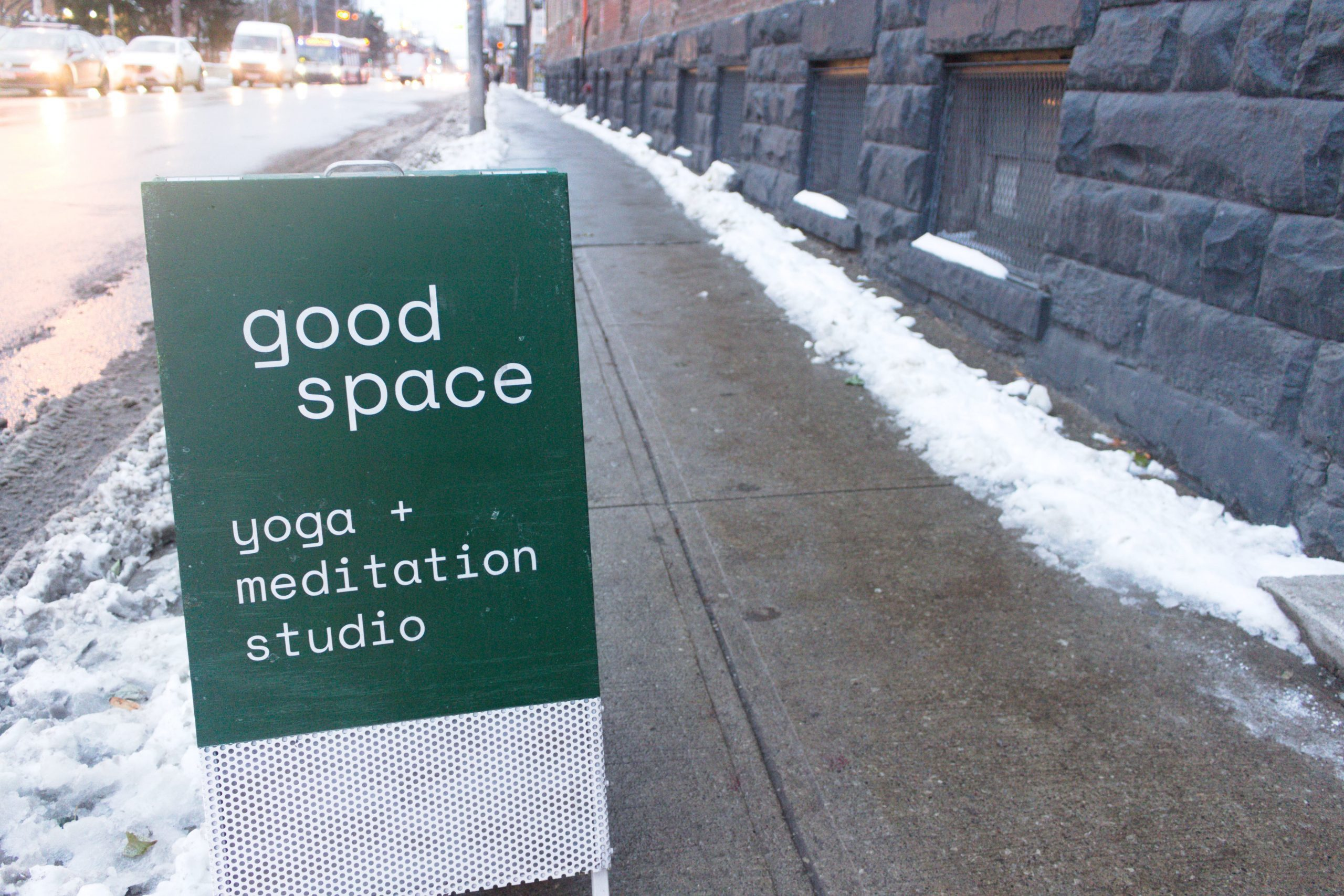 "Sign on snowy sidewalk reading ""Good space yoga and meditation studio""."