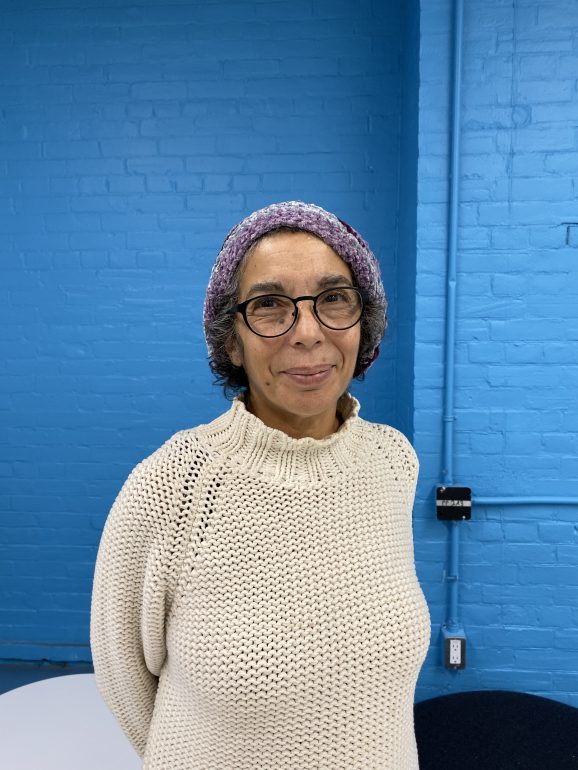 a woman stnads in front of a blue brick wall. she wears a light purple beanie and cream-coloured sweater.