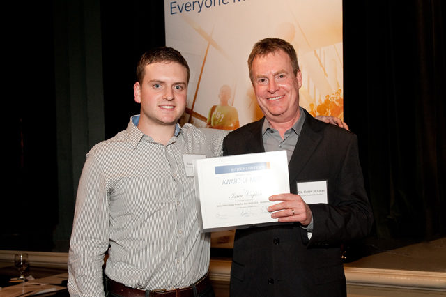 Two men standing and smiling, one holding certificate.