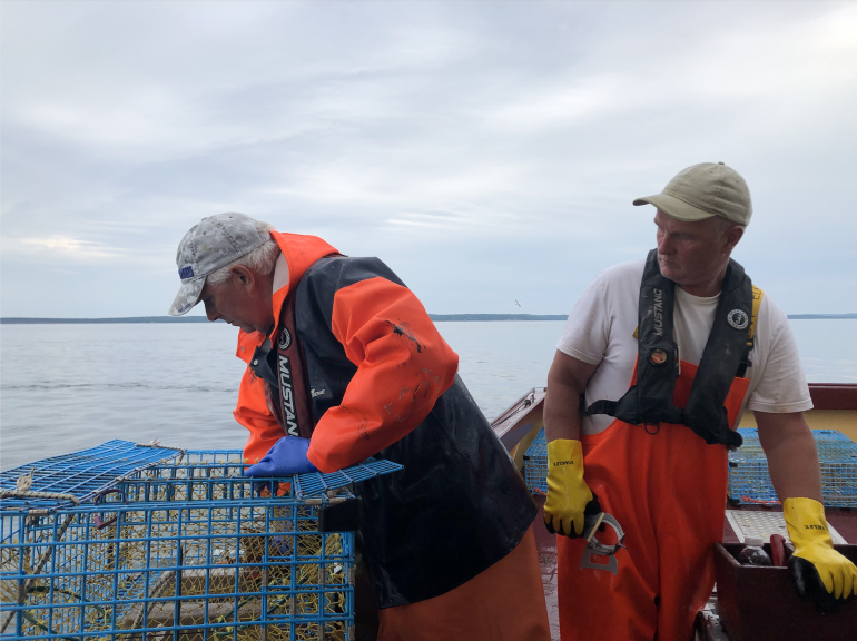 Two men in overalls on fishing boat look through blue cages.