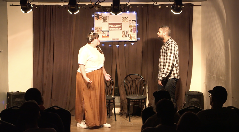 Man and woman on stage with black curtain and two chairs.