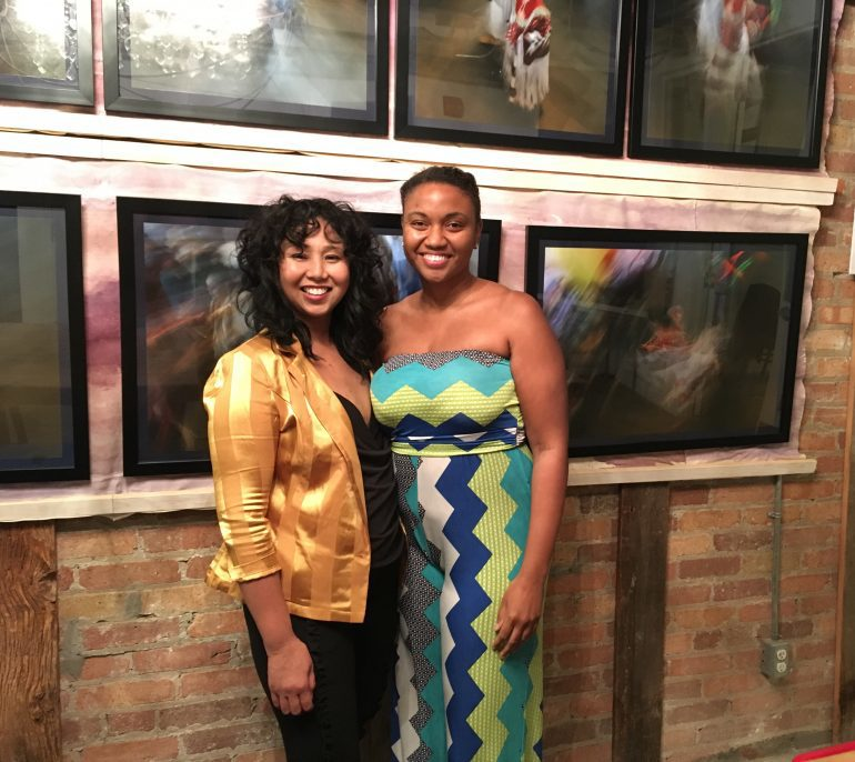 Two women smiling, standing against wall of paintings.