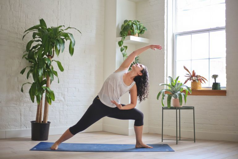 Woman on yoga mat surrounded by plants stretching.