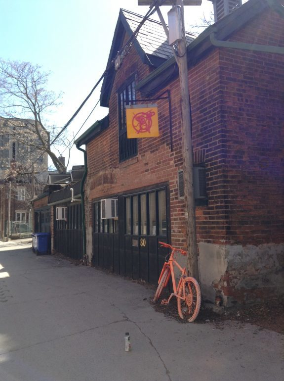 Exterior of brick building with orange bicycle.