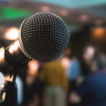 A microphone on a stage placed in front of an audience.