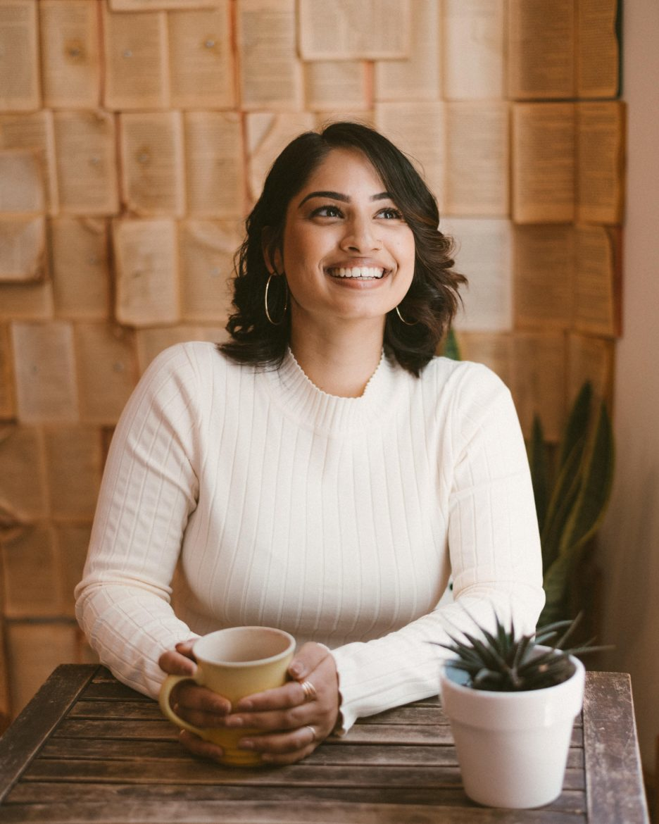Woman holding mug in front of wall covered in books, smiling and looking away