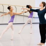 Two young girls in purple leotards doing ballet with instructor dressed in black.
