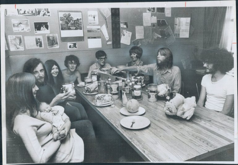 Black and white image of group sitting at restaurant table with woman holding baby.