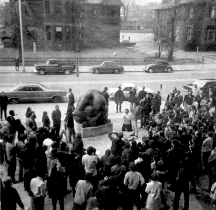 Black and white image of group gathered outside statue.