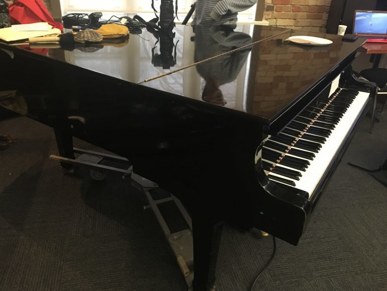 Black grand piano with various objects on top.