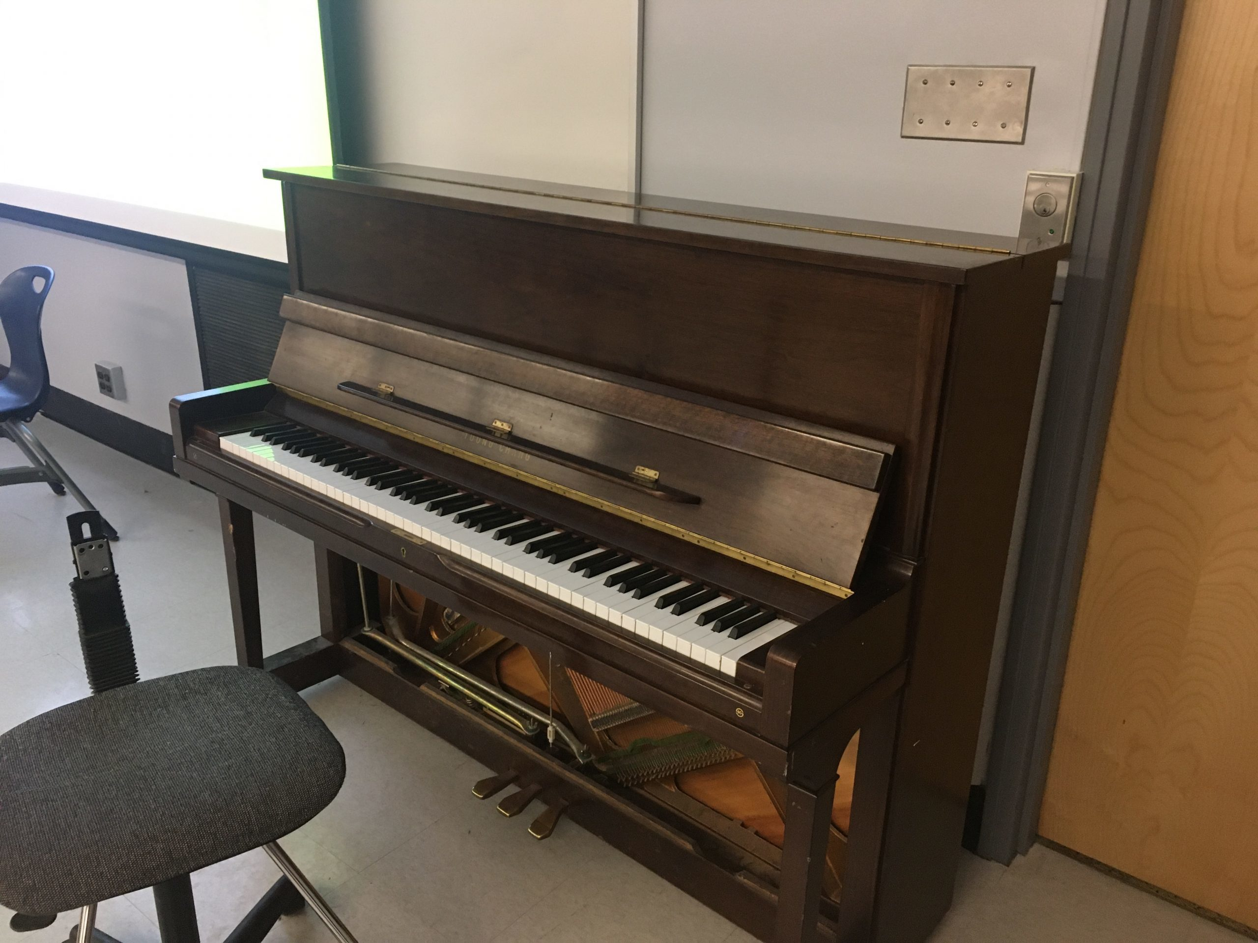 Piano in classroom with office chair in Kerr Hall South