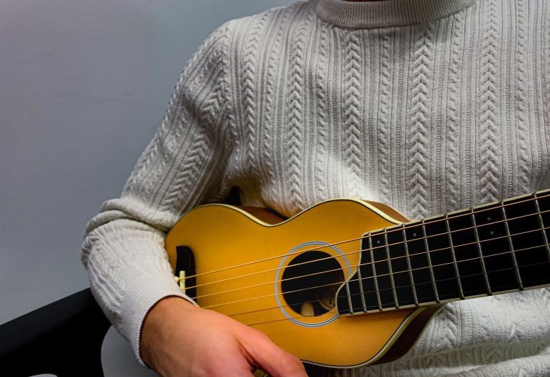 Closeup of a person's holding a guitar.