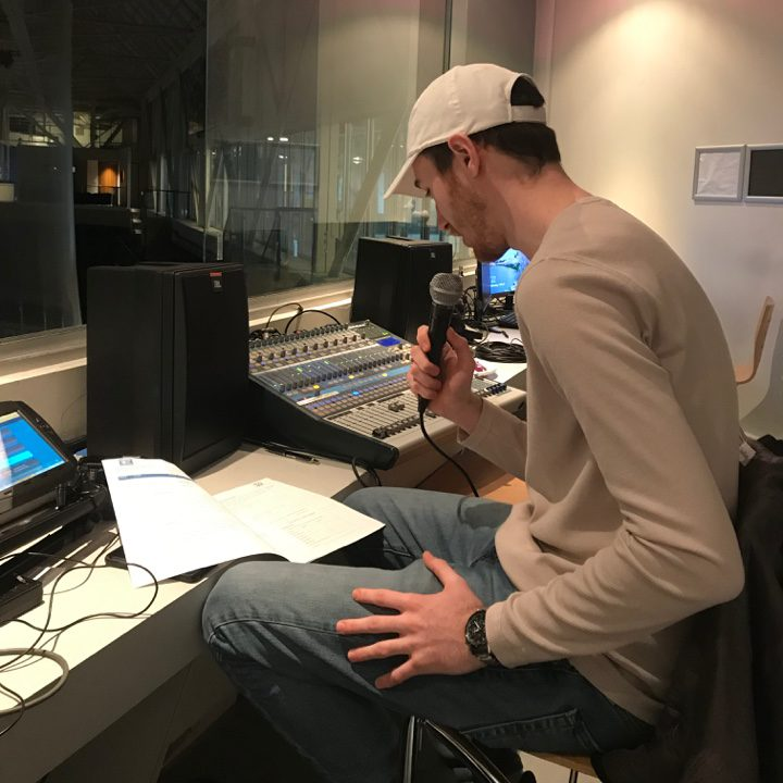 Braden Gibson holding a microphone practicing reads in a recording studio at the Mattamy Athletic Centre.