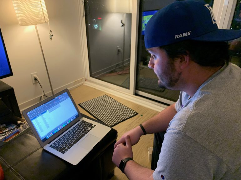 PA announcer Kevin MacDonald reading his announcer spreadsheet from a laptop screen in his living room