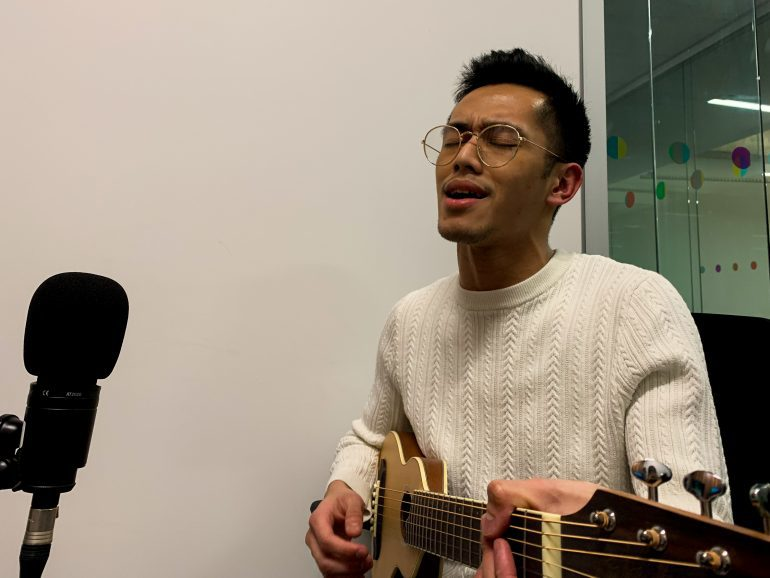 Christian Ocampo playing his music as Ryerson University holding a guitar singing into a microphone.