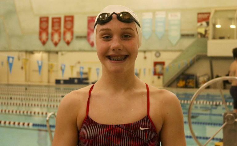 Katrina Bellio stands near the pool wearing a swim cap and goggles on her headsmiling after swim practice.